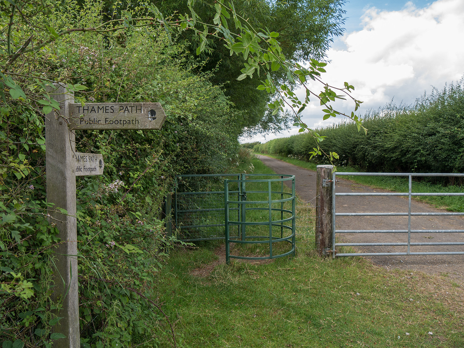 After a series of fields (to the right in this picture) the path reaches a tarmac road via a kissing gate