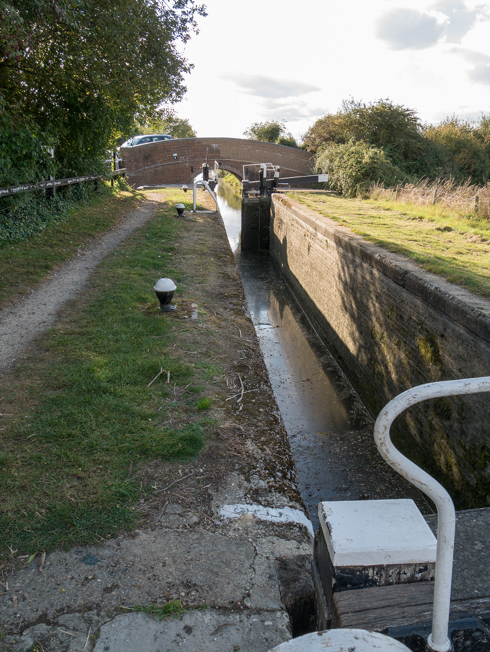 Typical narrow lock and half width gates at the far end. The dry lock walls indicate that the lock has not been used recently.