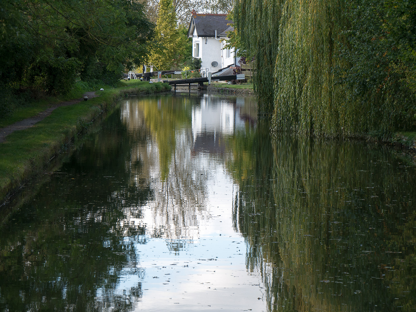 Reflections on the still water on the approach to a lock with the keeper's cottage nearby.