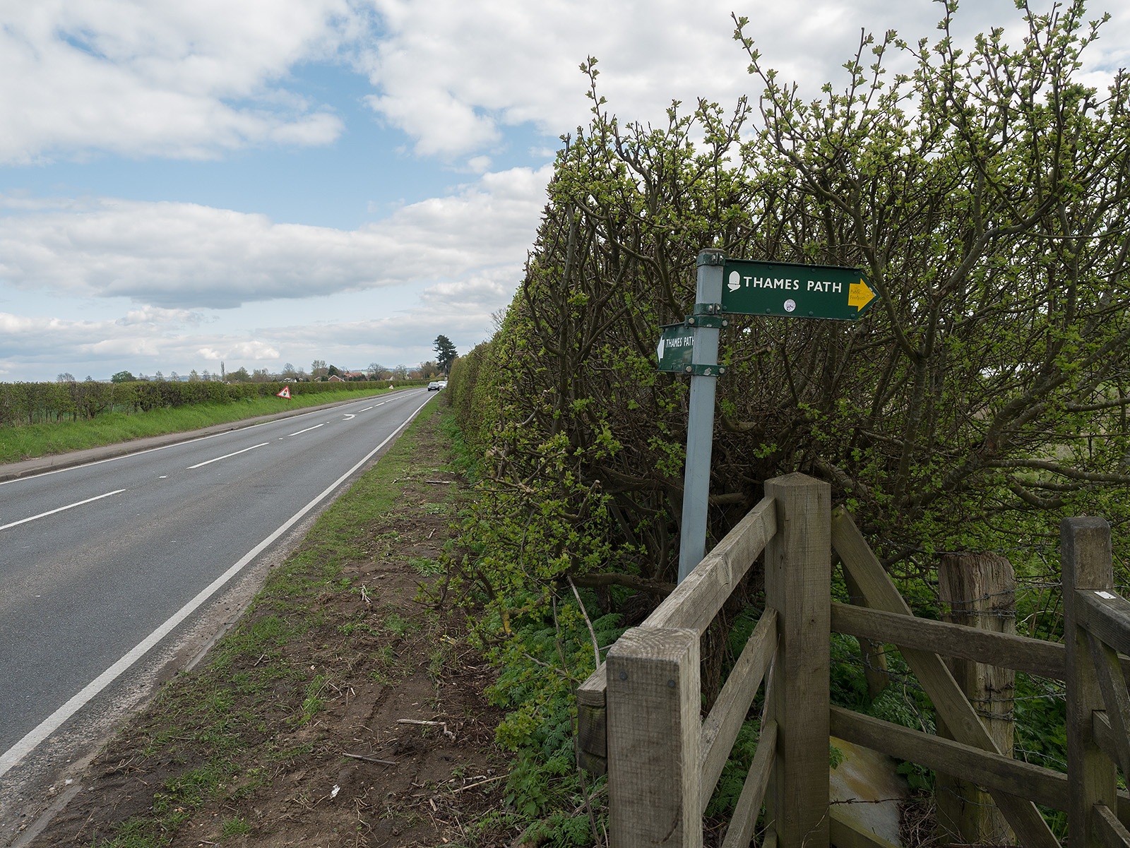 After a walk alongside the road, there is a gate into a field, as the path returns towards the riverside.